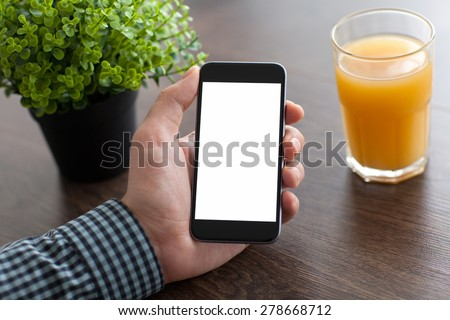 man hand holding a phone with isolated screen on the desk in the office - stock photo