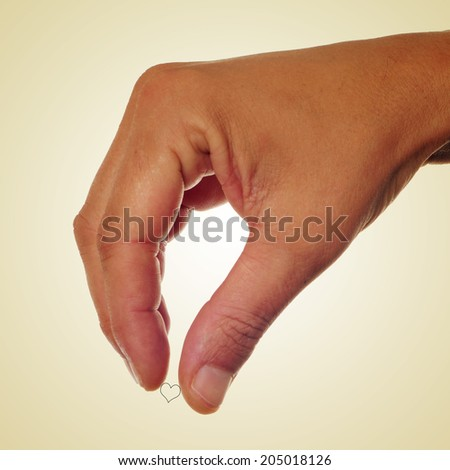 man hand holding a small heart drawn, with a retro effect - stock photo