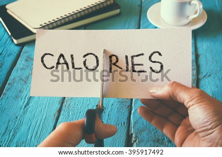 man hand holding card with the word calories. cutting calories and costs concept. retro style image - stock photo