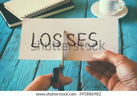 man hand holding card with the word losses. cutting losses and costs concept. retro style image - stock photo