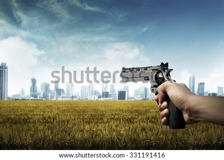 Man hand holding gun, aim to the city - stock photo
