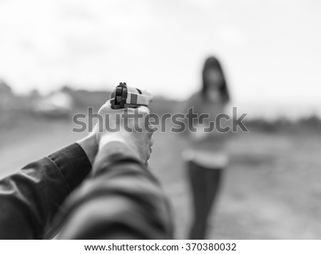 Man hand holding gun aim to woman. Selective focus with shallow depth of field. Black and white toning. - stock photo