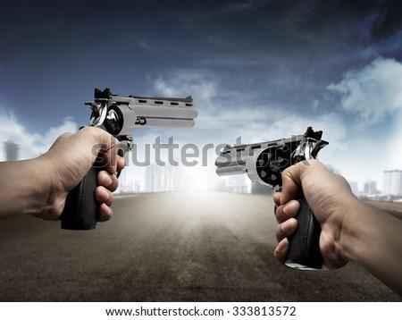 Man hand holding gun, aiming to the city - stock photo