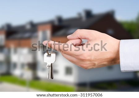 Man hand holding keys with to new house. Home shape chrome pendant  - stock photo