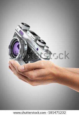 Man hand holding object ( Vintage silver photo camera ) High resolution