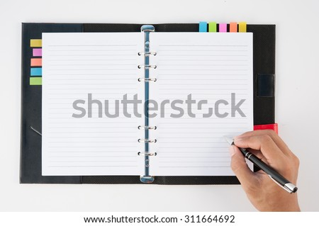Man hand holding pen and writing notebook  on white background for text and background.copy space - stock photo