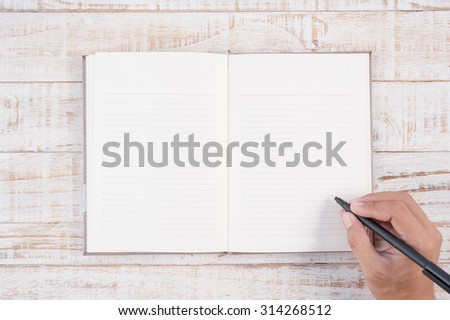 Man hand holding pencil and writing notebook  on wood table for text and background.copy space - stock photo