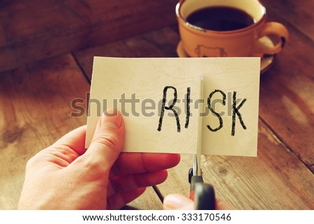 man hand holding scissors and cutting paper card with the word risk .  - stock photo