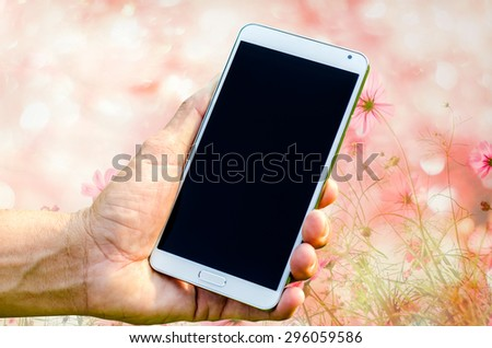 Man hand holding smartphone against on bokeh background soft focus. - stock photo