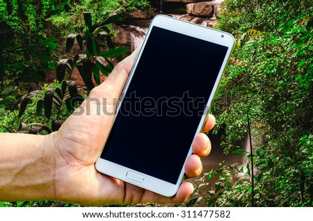 Man hand holding smartphone against on nature background soft focus. - stock photo