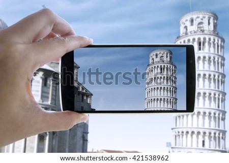 Man hand holding smartphone and taking photo of Pisa Tower - stock photo