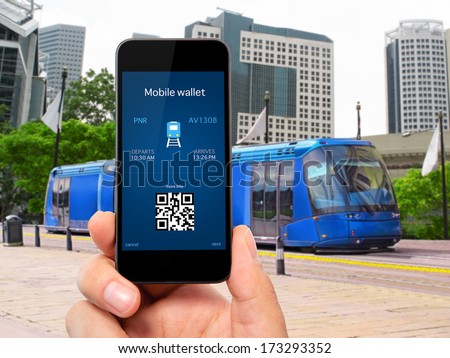 man hand holding the phone touch with a mobile wallet and train ticket against the blue train to the city - stock photo
