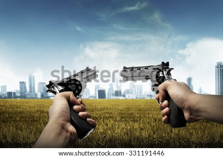 Man hand holding two gun, aiming to the city - stock photo