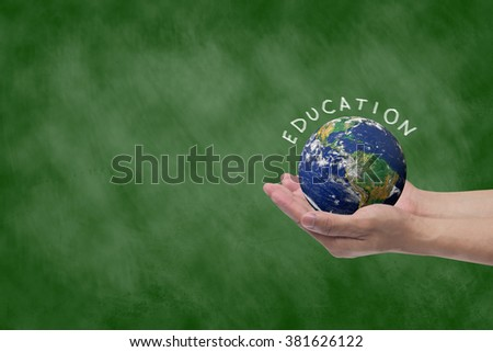 man hand holding world on chalkboard background.giving knowledge/education to poverty population concept idea:support,improve,development ability conceptual:Elements of this image furnished by NASA.  - stock photo