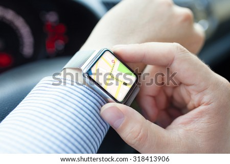 Man hand in the car with watch and app navigation on the screen - stock photo