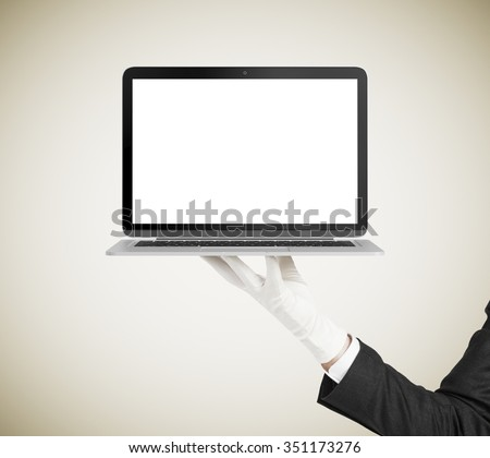 Man hand in white glove holding laptop with blank screen, mock up - stock photo