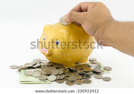man hand inserting a coin into a piggy bank - stock photo
