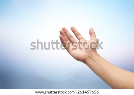 man hand open palm gesture for receive power form paradise over glowing background:human outstretched arm and pray to heaven for forgiveness.relation of god,people,soul concept:spiritual person symbol - stock photo