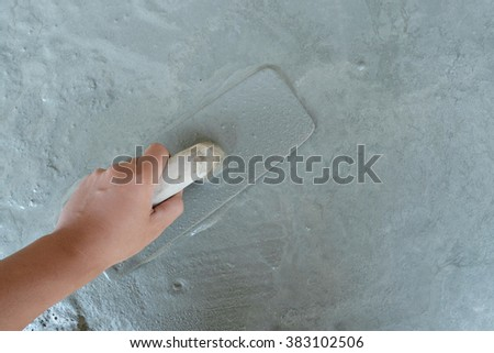 man hand plastering a wall with trowel, Selective focus. - stock photo