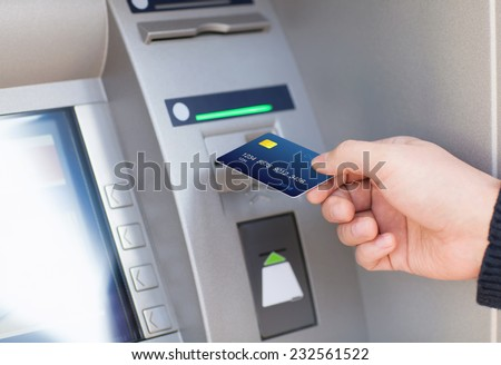 man hand puts credit card into ATM - stock photo