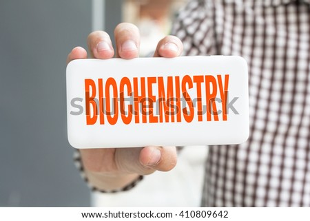 Man hand showing BIOCHEMISTRY word phone with  blur business man wearing plaid shirt. - stock photo