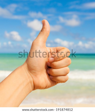 Man hand showing okay sign at the beach.