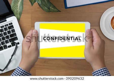 man hand Tablet with Confidential Concept screen and coffee cup - stock photo