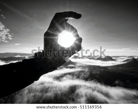Man hand touch Sun. Misty daybreak in a beautiful hills. Peaks of hills are sticking out from foggy background. Black and white photo