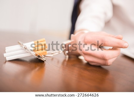 Man hand with handcuffs and cigarettes on the table. The concept of smoking dependence. - stock photo