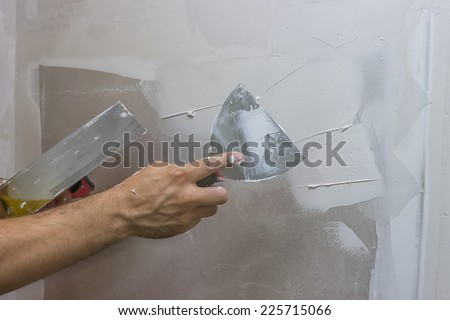 man hand with trowel plastering a wall, skim coating plaster walls - stock photo