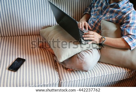 man hand working with laptop on sofa, Hands multitasking man working on laptop connecting internet,  finger typing on keyboard laptop computer sitting at wooden table.Success life - stock photo