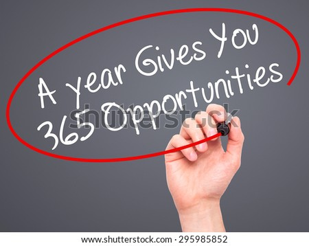 Man Hand writing A year Gives You 365 Opportunities with black marker on visual screen. Isolated on grey. Business, technology, internet concept. Stock Photo - stock photo