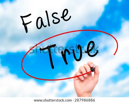 Man Hand writing an choosing True instead of False with black marker on visual screen. Isolated on sky. Business, technology, internet concept. Stock Image - stock photo