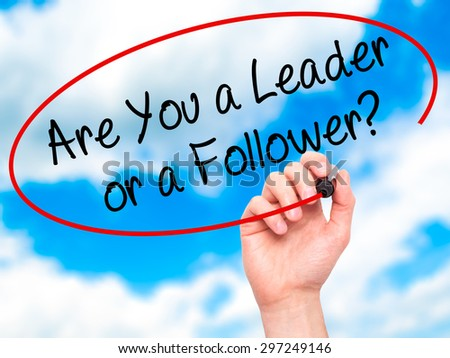 Man Hand writing Are You a Leader or a Follower? with black marker on visual screen. Isolated on sky. Business, technology, internet concept. Stock Photo - stock photo