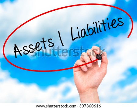 Man Hand writing Assets Liabilities with black marker on visual screen. Isolated on sky. Business, technology, internet concept. Stock Photo - stock photo