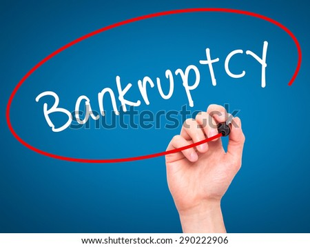 Man Hand writing Bankruptcy with black marker on visual screen. Isolated on blue. Business, technology, internet concept. Stock Image  - stock photo