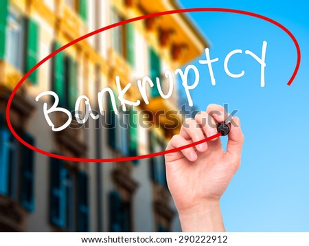 Man Hand writing Bankruptcy with black marker on visual screen. Isolated on buildings. Business, technology, internet concept. Stock Image  - stock photo