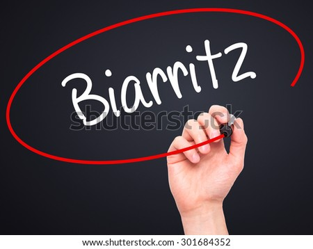 Man Hand writing Biarritz  with black marker on visual screen. Isolated on black. Business, technology, internet concept. Stock Photo - stock photo