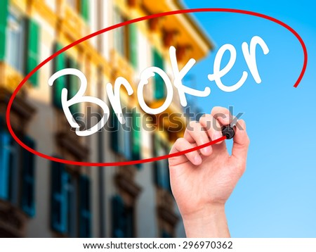 Man Hand writing Broker with black marker on visual screen. Isolated on city. Business, technology, internet concept. Stock Photo - stock photo