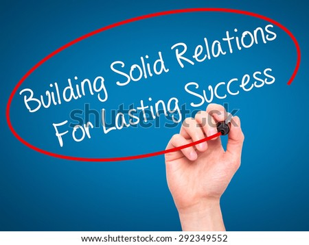 Man Hand writing Building Solid Relations For Lasting Success with black marker on visual screen. Isolated on blue. Business, technology, internet concept. Stock Image - stock photo