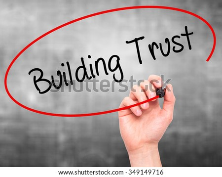 Man Hand writing Building Trust with black marker on visual screen. Isolated on background. Business, technology, internet concept. Stock Photo - stock photo