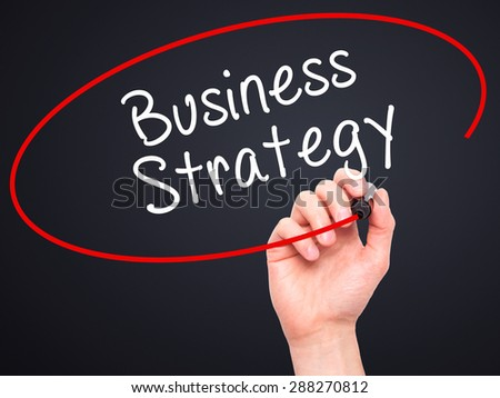Man Hand writing Business Strategy with black marker on visual screen. Isolated on black. Business, technology, internet concept. Stock Image - stock photo