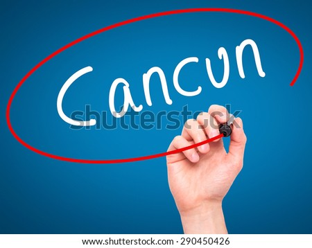 Man Hand writing Cancun with black marker on visual screen. Isolated on blue. Travel, technology, internet concept. Stock Image - stock photo