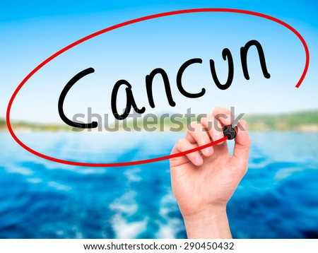 Man Hand writing Cancun with black marker on visual screen. Isolated on nature. Travel, technology, internet concept. Stock Image - stock photo
