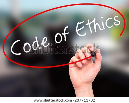 Man Hand writing Code of Ethics with black marker on visual screen. Isolated on office. Business, technology, internet concept. Stock Image - stock photo