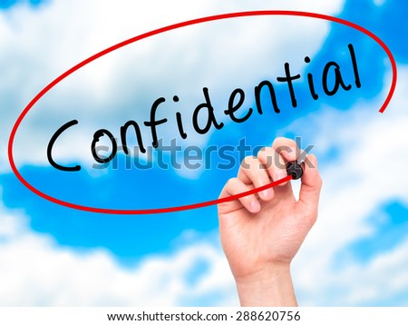 Man Hand writing Confidential with black marker on visual screen. Isolated on sky. Business, technology, internet concept. Stock Image - stock photo