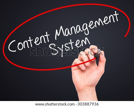 Man Hand writing Content Management System  with black marker on visual screen. Isolated on black. Business, technology, internet concept. Stock Photo - stock photo