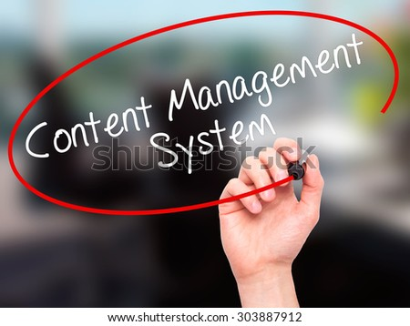 Man Hand writing Content Management System  with black marker on visual screen. Isolated on office. Business, technology, internet concept. Stock Photo - stock photo