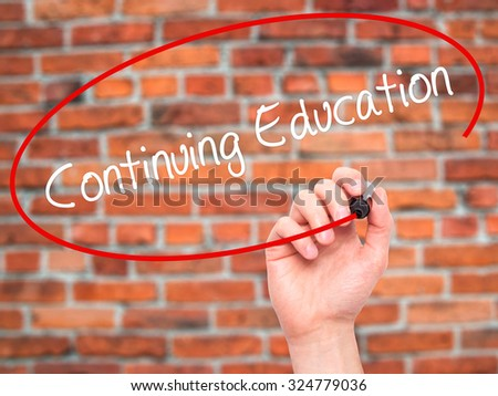 Man Hand writing Continuing Education with black marker on visual screen. Isolated on bricks. Business, technology, internet concept. Stock Photo - stock photo