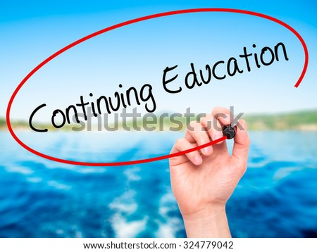 Man Hand writing Continuing Education with black marker on visual screen. Isolated on nature. Business, technology, internet concept. Stock Photo - stock photo